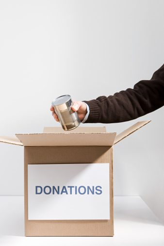Person putting can in donation box