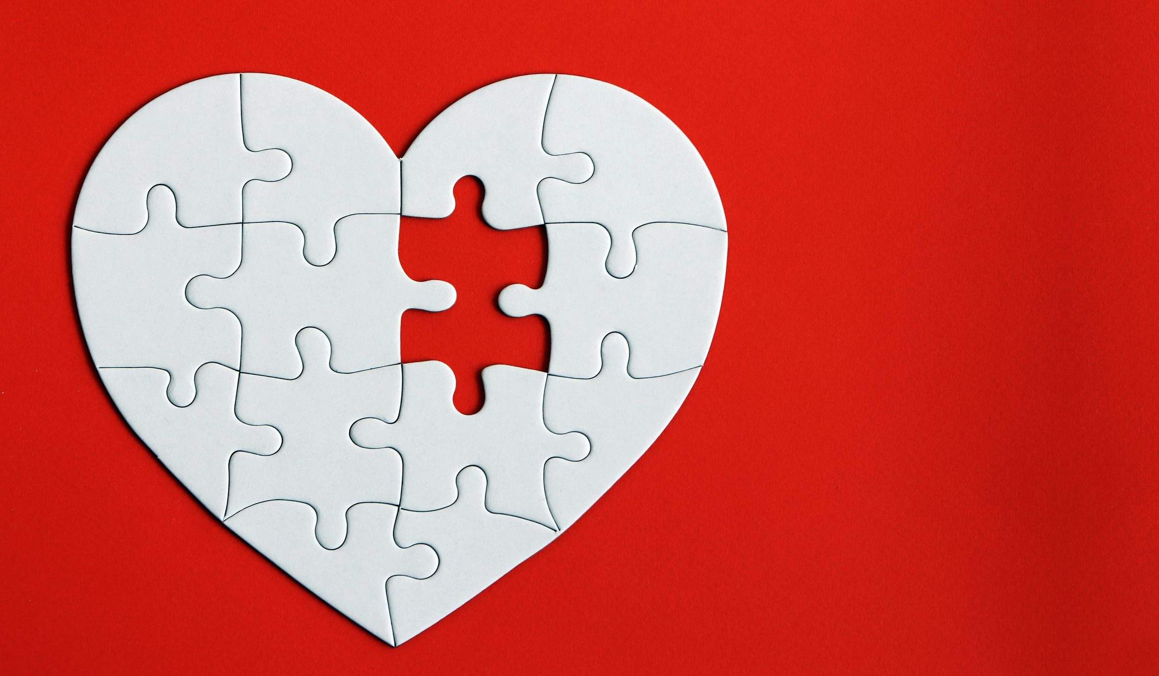 Heart puzzle on the red background