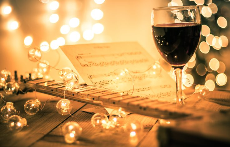 wine glass by music sheet and lights