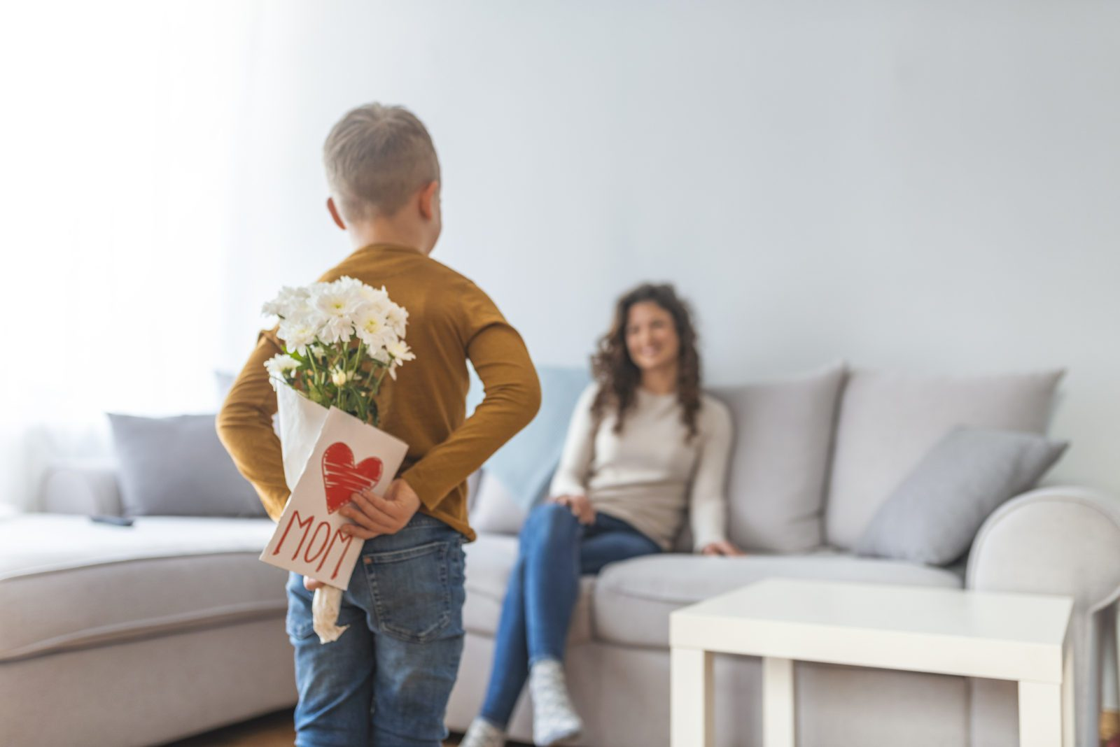 Happy mother's day! Child boy gives a bouquet of flowers and gift