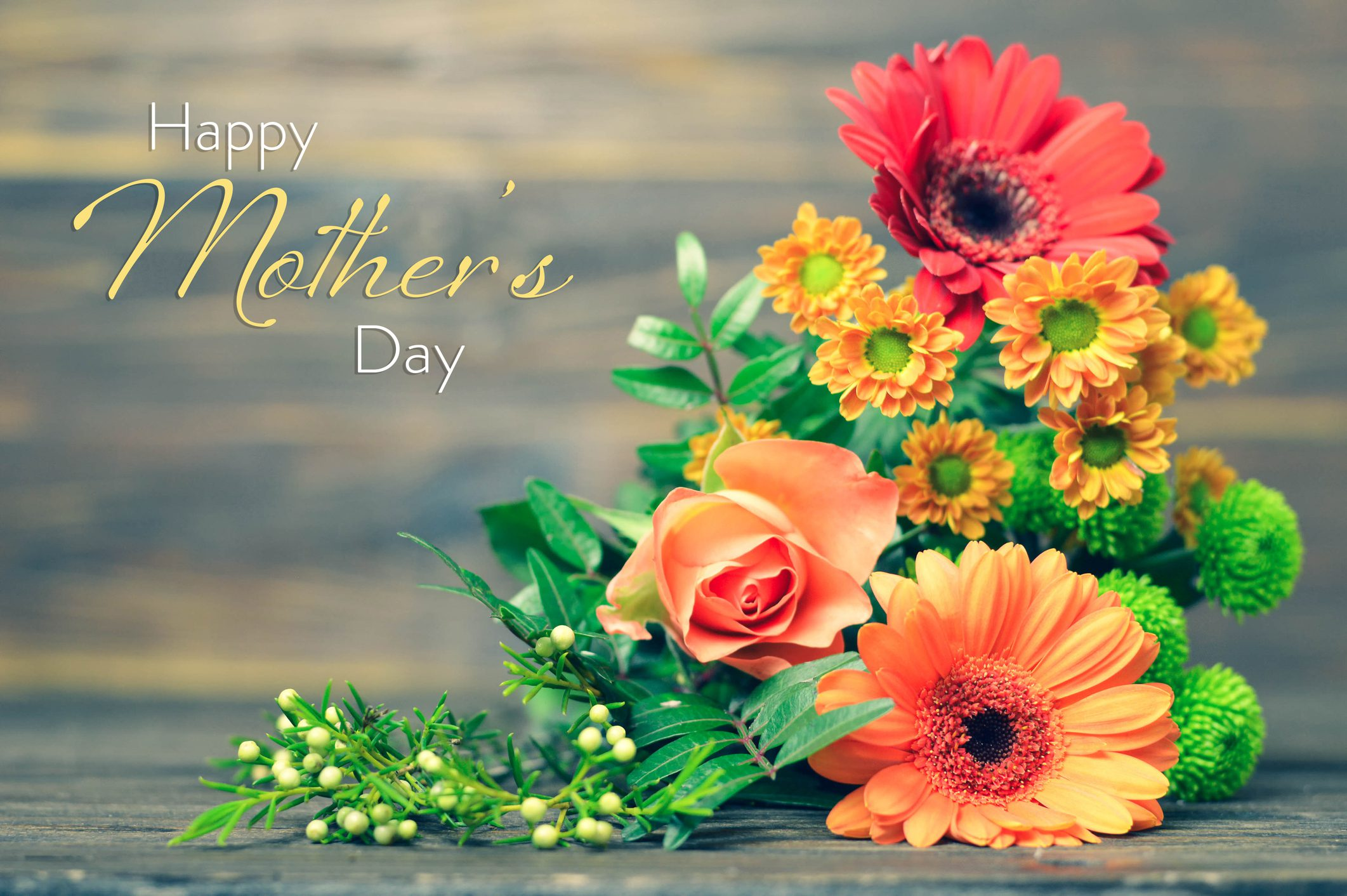 Happy Mothers Day card with flowers on wooden background