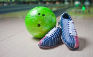 Sport Shoes and green ball on floor in bowling club
