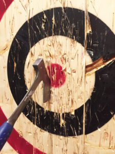A large metal axe is embedded into a wooden target.