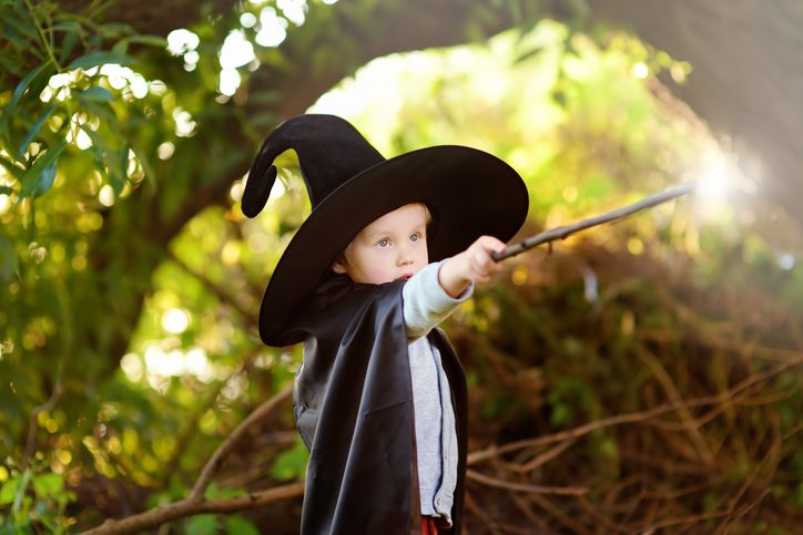 Little boy dressed as a wizard with a wand in his hand - wizardry getty images 1163926785