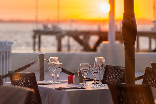 Close-up of outdoor place setting during sunset at waterfront dining.