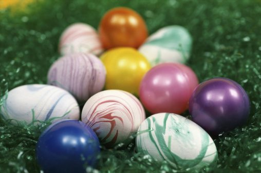 Colorful Easter eggs in a bed of green Easter grass.