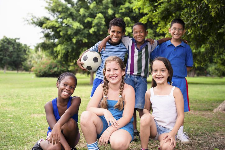 Smiling culturally-diverse group of children on soccer field with soccer ball looking at camera. Summer camp fun.