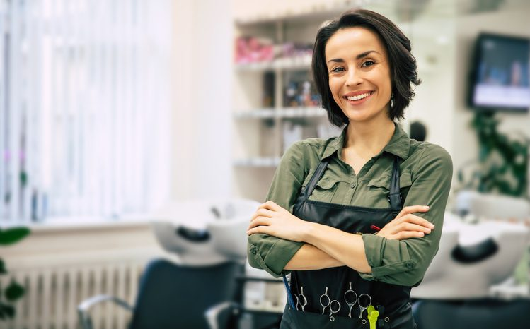 Portrait of a gorgeous young hairstylist standing with folded arms near her workplace in the salon.