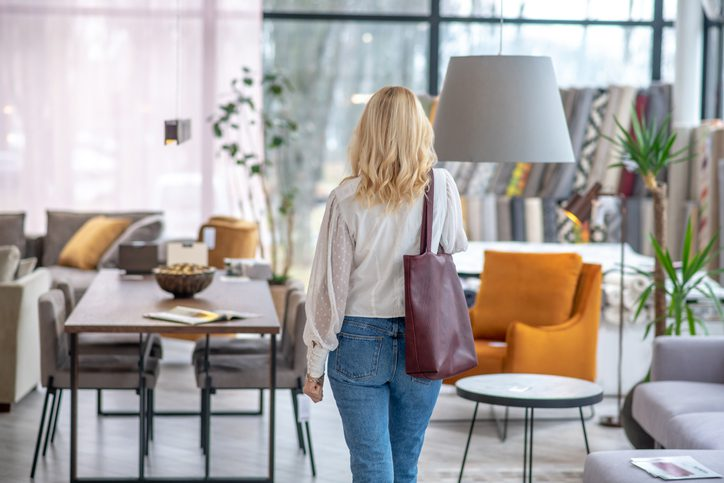 All for the house. Woman in a white blouse with a burgundy bag on her shoulder, standing with her back in the furniture salon.
